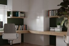 a very stylish minimalist home office with sleek white cabinets and a built-in stained desk, a chair and potted plants