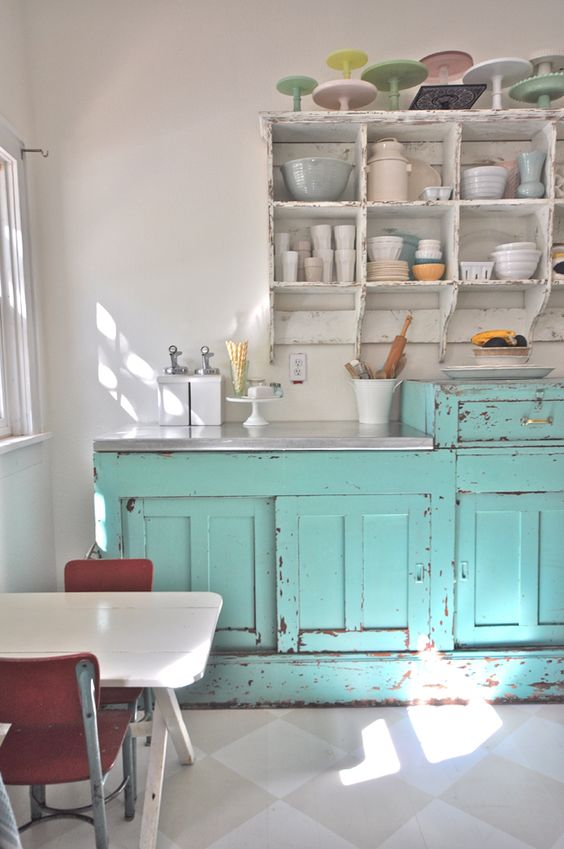 a vintage kitchen with shabby light blue and white furniture, a small dining set and pastel porcelain on top the cabinets