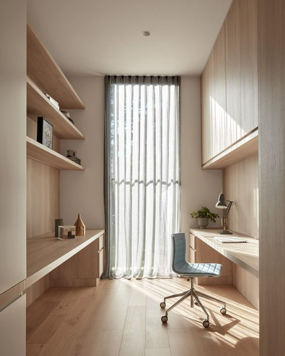 a welcoming minimalist home office with a built-in slek storage unit, open shelves, built-in desks and a blue chair plus a curtain