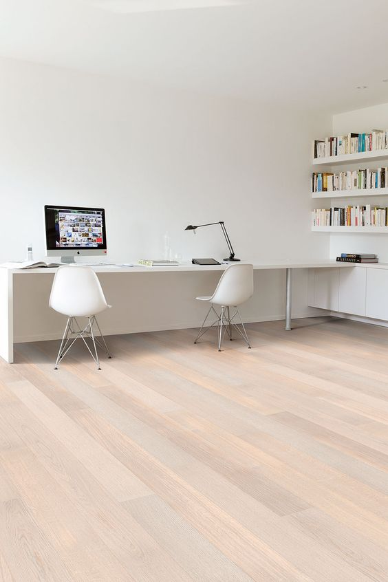 a white minimalist home office with bookshelves, a long desj and white chairs plus a black table lamp is a cool space
