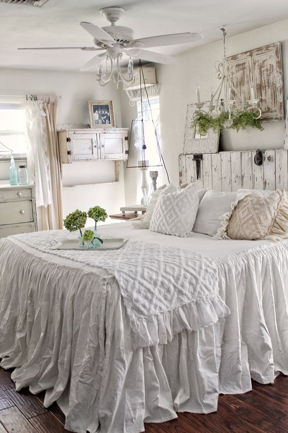 a white shabby chic bedroom with a wooden bed and a wooden screen, a cabinet, a white fan and a moss chandelier and greenery