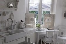 a white shabby chic kitchen with vintage cabinets, a crystal chandelier, open shelving units and shutters is chic