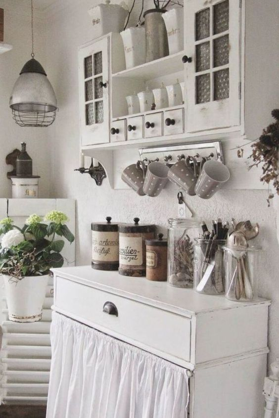 a white shabby chic kitchen with vintage furniture, a cabinet with a curtain, potted blooms, a metal pendant lamp