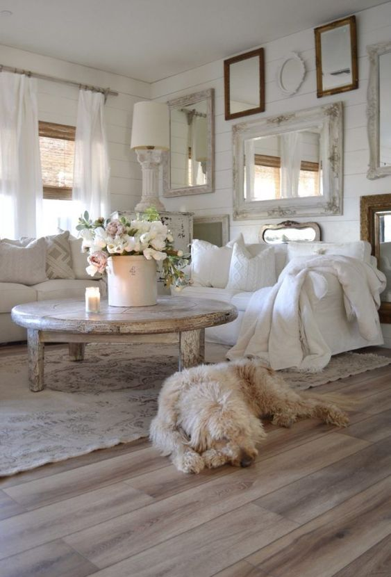 a white shabby chic living room with a gallery wall of mirrors, white furniture, a shabby table and lamps and blooms
