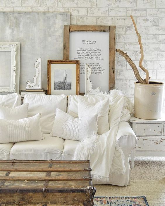 a white shabby chic living space with a gallery wall, a white sofa, a shabby sideboard and a wooden chest