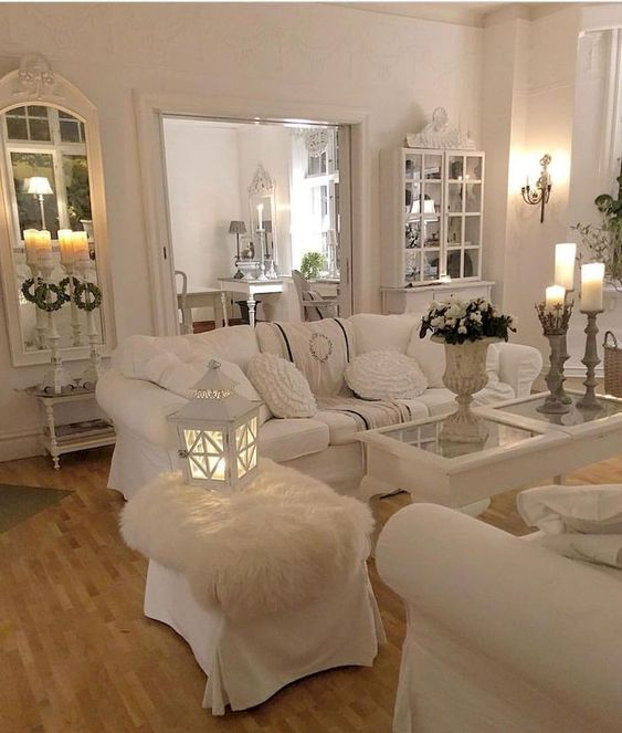 a white shabby chic living space with elegant mirrors and stylish furniture, candles, candle lanterns and white bloom