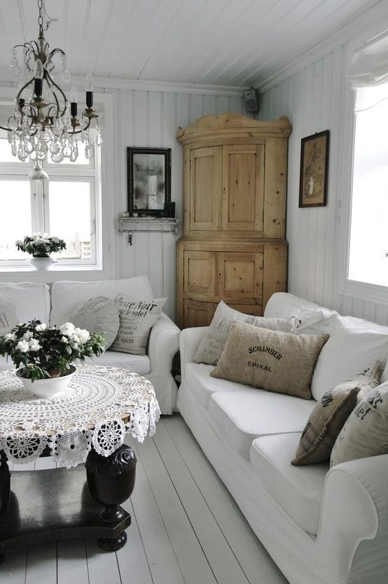 a white vintage to shabby chic living room with white sofas, a wooden wardrobe, a crystal chandelier, a black table, a crochet tablecloth and blooms