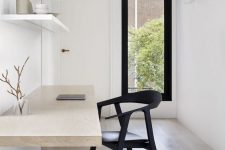 an airy minimalist home office with open shelves, a floating desk, a black chair and a narrow window for a view