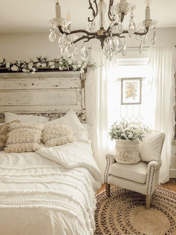 an airy white shabby chic bedroom with a shabby headboard, vintage furniture, a crystal chandelier and neutral blooms