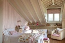 an attic shared shabby chic kids' room with a pink striped wall, neutral furniture, pink floral textiles and a curtain is very cozy