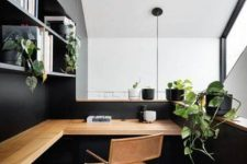 an elegant minimalist home office in grey and black, with open storage units, a stained corner desk and a leather chair plus potted greenery