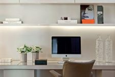 an elegant minimalist white home office with sleek cabinety, an open shelf with built-in lights, a leather chair and some art
