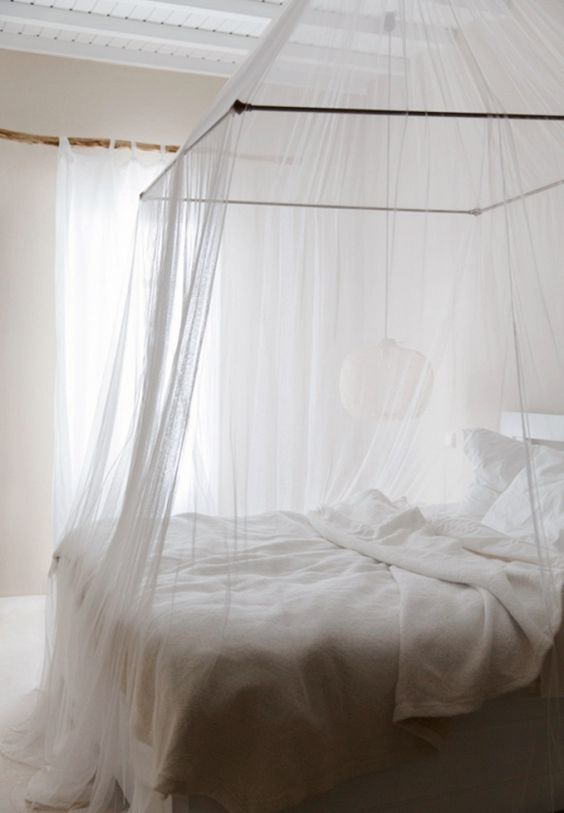 an ethereal white bedroom with a mosquito net canopy over the bed that gives a summer feel to the space