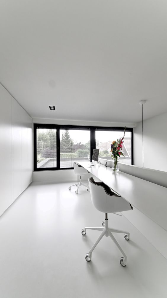an ultra-minimalist home office in black and white, with a floor to ceiling window, a floating shared desk and black and white chairs