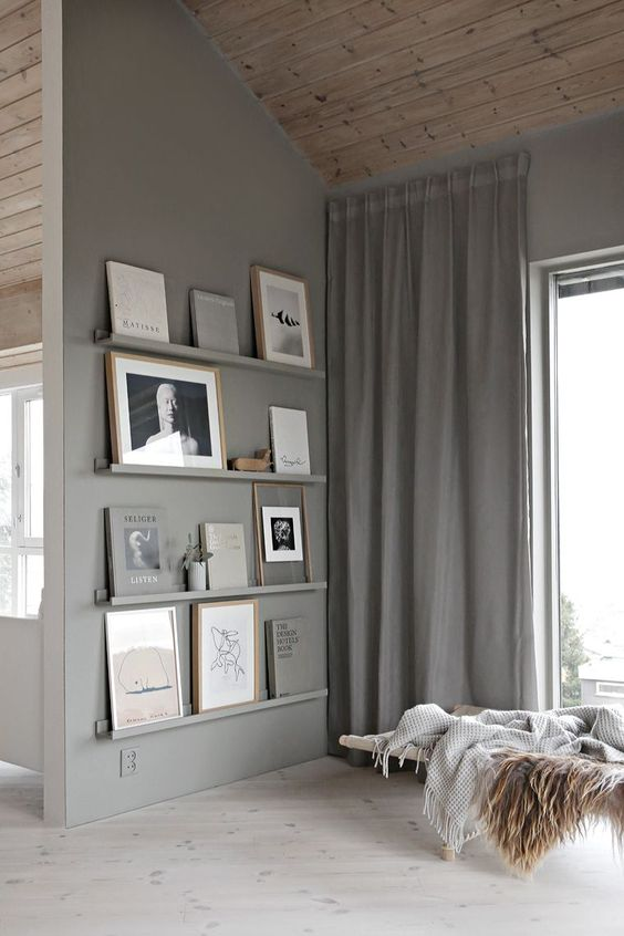grey ledges match the grey wall and show off books and artworks beautifully and seamlessly looking chic