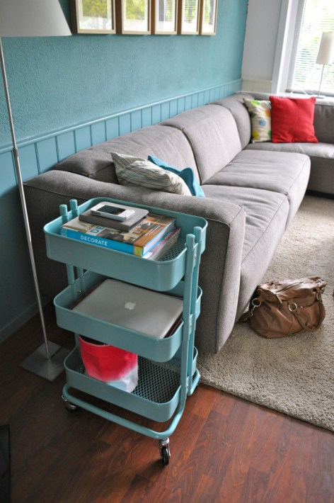 The cart is a great organizer for books and computer devices in a living room.