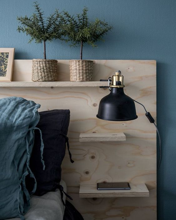 a Nordic bedroom with a blue accent wall, a bed with a storage headboard, potted plants, a large black IKEA Ranarp sconce on the headboard