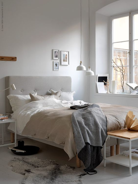 a Nordic bedroom with simple and laconic furniture, a grey upholstered bed, white pendant lamps over the space