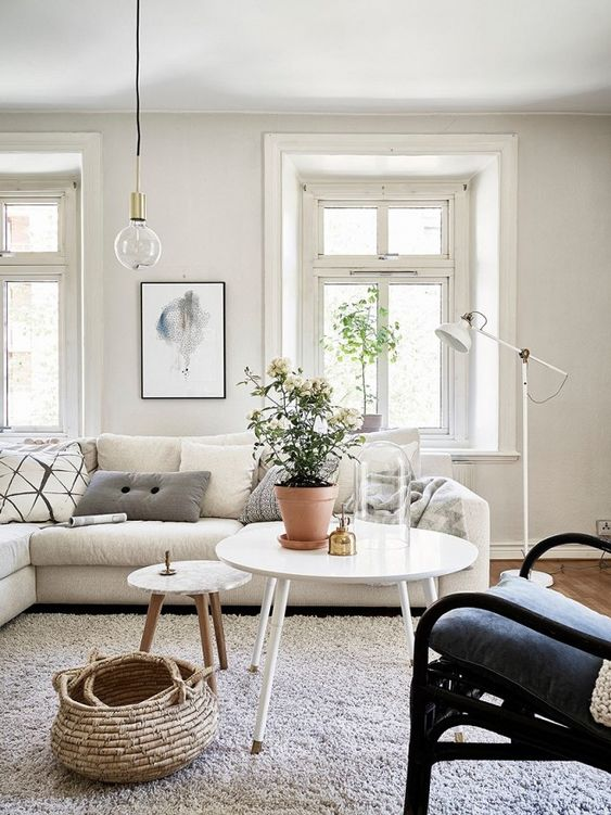 a Scandinavian living room with a large neutral sectional, a dark chair, white tables, a basket and an IKEA Ranarp floor lamp