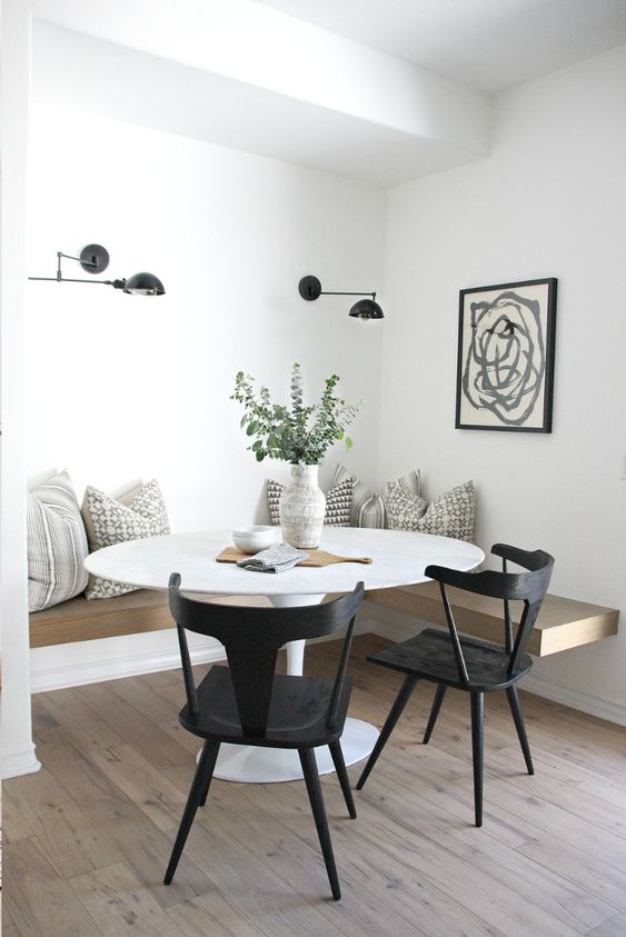 a beautiful Scandinavian dining space with a floating bench, a round table, black chairs, black sconces and a graphic art