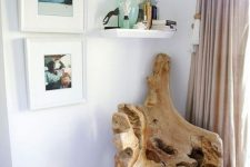 a beautiful driftwood chair, some ocean-inspired artworks and a shelf with corals create a sea-inspired nook here