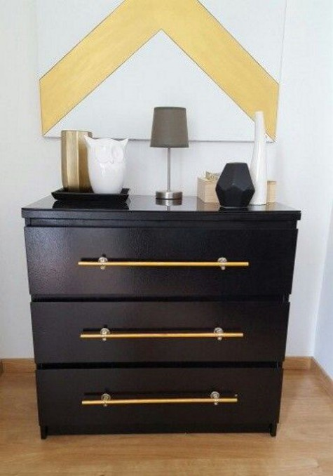 a black IKEA Malm accessorized with large brass handles brings a trendy and chic feel