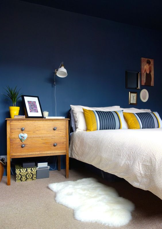 a bold bedroom with navy walls, stylish mid-century modern furniture, white IKEA Ranarp wall sconces