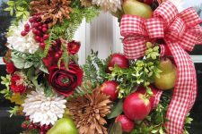 a bold fall wreath of greenery, natural and dried blooms, faux fruit and berries and a bold plaid bow
