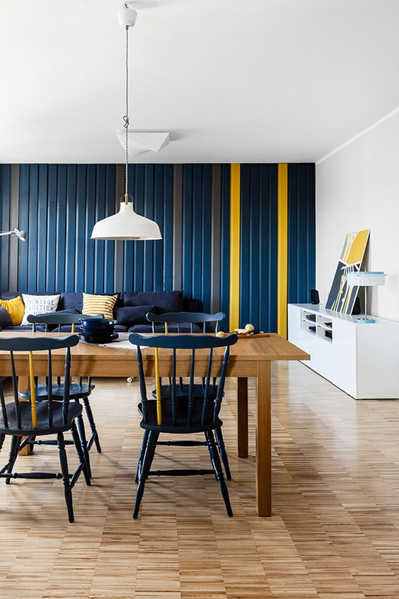 a bold navy and yellow open layout for a living and dining room, white pendant IKEA Ranarp lamps over the dining space