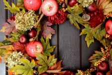 a bright and chic fall wreath of faux foliage, apples, berries, dried hydrangeas, cinnamon sticks will have a fall aroma