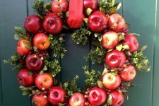 a bright fall wreath of bold apples, greenery, berries and a red ribbon for accenting your front door and make it fall-like