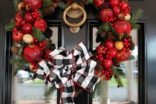 a bright fall wreath of faux fruit, berries, pinecones, evergreens and a large plaid bow on top