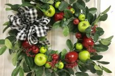 a bright wreath of foliage, green and red apples and a plaid bow is a cool decoration in farmhouse style