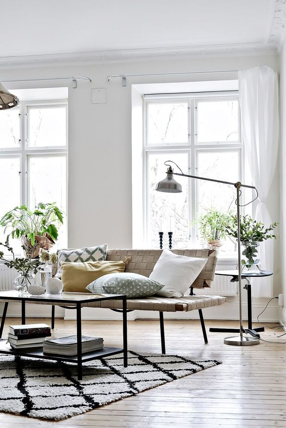 a catchy Nordic space with a leather bench, a table, an IKEA Ranarp floor lamp and greenery around