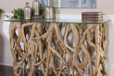 a chic console table of lots of driftwood and a glass tabletop is a refined and cool idea for a beachy or eco-friendly interior