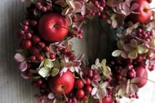 a chic fall wreath of dried blooms, berries and red apples is a small and cute decoration for your porch