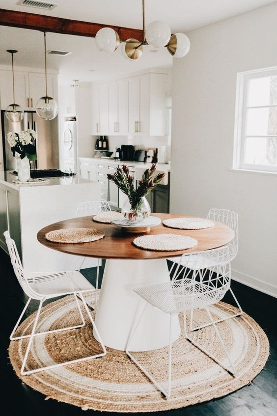 a chic modern dining space with a round table, metal chairs, a jute rug, a modern chandelier and some blooms