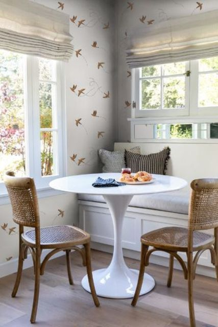 a cool and cozy dining area with a built-in bench, a round table, woven chairs, beautiful wallpaper and views