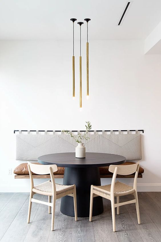 a cool modern dining area with a floating bench with a soft back, a black round table, woven chairs and a lovely gold tube lamp