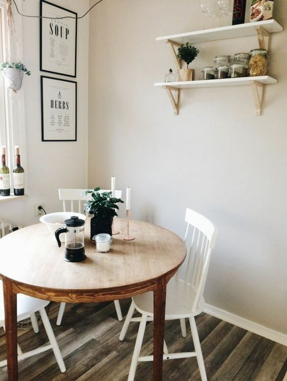 a cozy dining nook with a stained round table, white chairs, open shelves and some greenery in pots has everything necessary