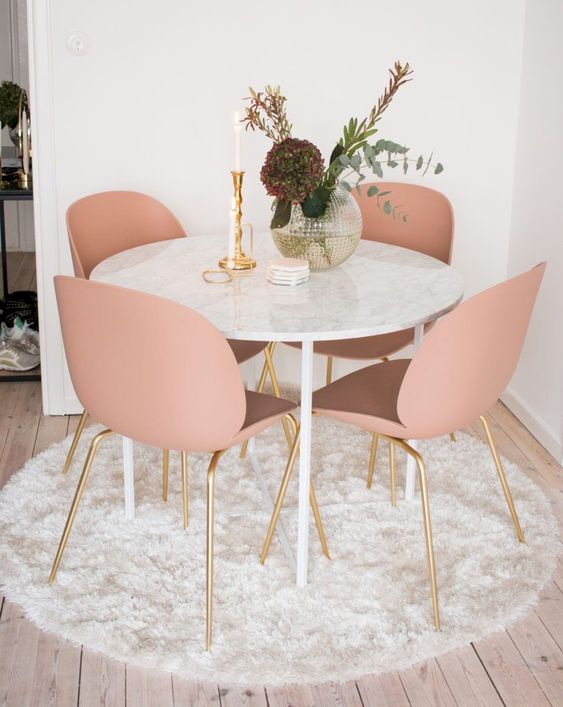 a cozy glam dining nook with a round table, pink chairs, a vase with blooms and a candle plus a fluffy rug is very cool