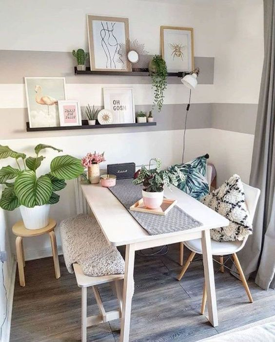 a cute and cozy dining nook with a table, chairs and a bench, open shelves, some artworks, potted greenery is lovely