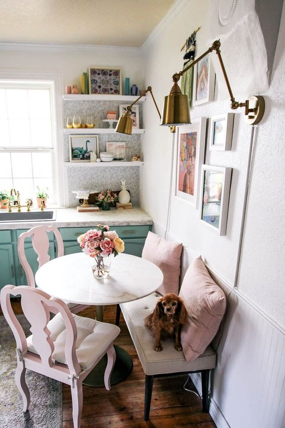 a cute small nook with a neutral bench, pink chairs and pillows, a round table and a lovely bright gallery wlal
