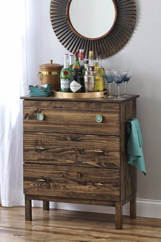 a dark stained IKEA Tarva dresser with thin pulls and turquoise knobs is a stylish piece