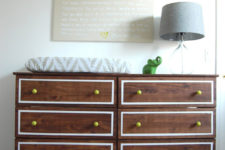 a dark stained IKEA Tarva dresser with white inlays and bright yellow knobs is a stylish dressing table