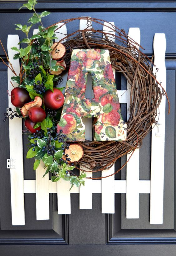 a farmhouse fall wreath of vine, appes and apple slices, berries, foliage, a bright paper mache monogram