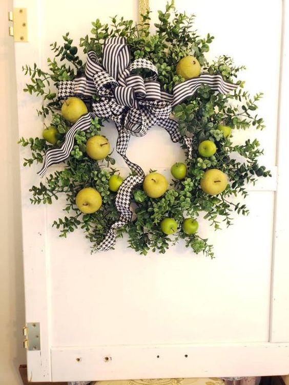 a fun and bright fall wreath of boxwood, green and yellow apples and printed bows for a colorful touch on your door