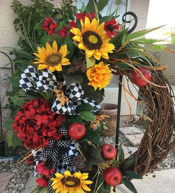 a fun fall wreath of vine, faux blooms, apples, grasses and leaves and some printed black and white bows and ribbons