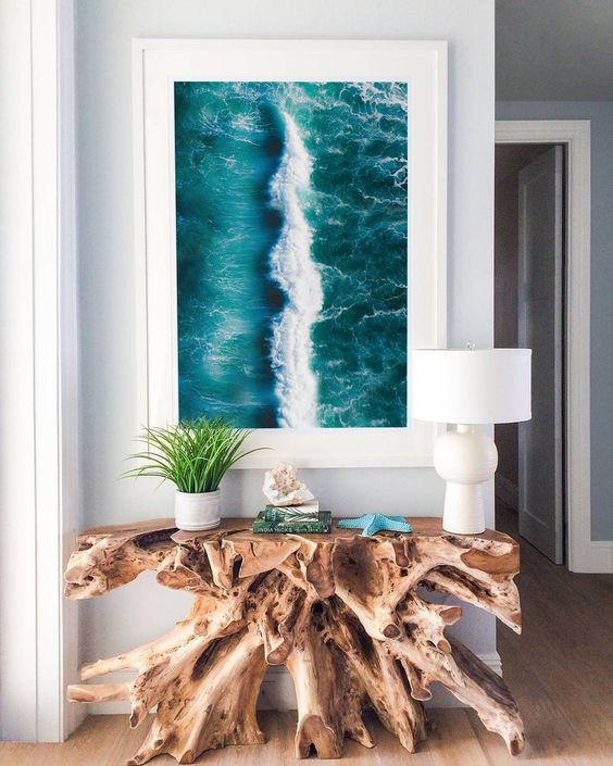 a gorgeous driftwood console table and an ocean print turn the entryway into a fantastic seaside space and they look wow