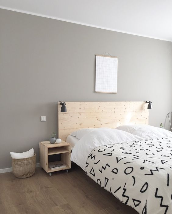 a laconic minimalist bedroom with light-colored wooden furniture, a basket, artworks and black IKEA Ranarp sconces